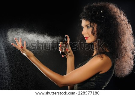 A portrait of a beautiful woman spraying perfume on black background  - stock photo
