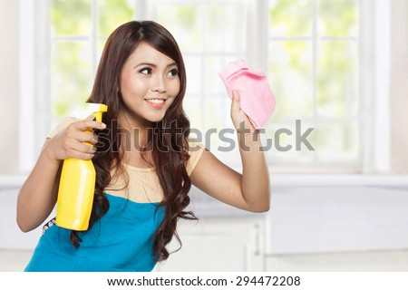 A portrait of a beautiful young asian woman doing chores, holding sprayer and pink rag - stock photo