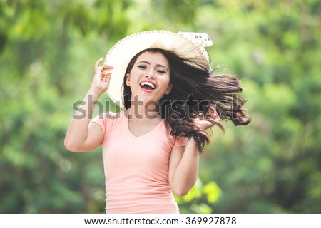 A portrait of a beautiful young asian woman wearing round hat on a park - stock photo