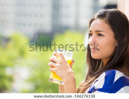 A portrait of a beautiful young female relaxing on a balcony on a sunny summer day, drinking orange juice, in her new apartment, background of a city scenery and green trees. Urban lifestyle.