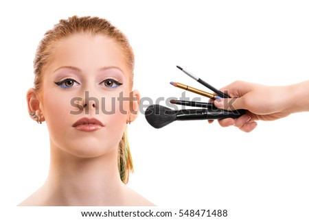A portrait of a beautiful young girl getting her make up applied, isolated on white background.