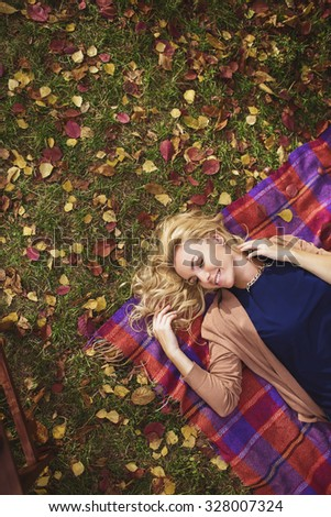 A Portrait of a beautiful young girl lays on a plaid in autumn - stock photo