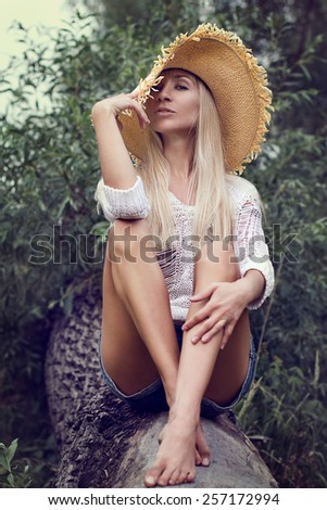 A portrait of a beautiful young woman sitting on a tree - stock photo