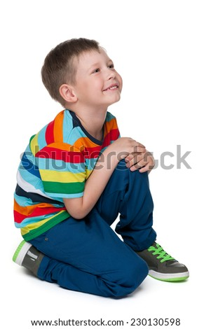 A portrait of a blond little boy in a striped shirt - stock photo
