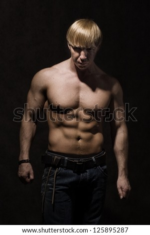 A portrait of a bodybuilder man in a studio.