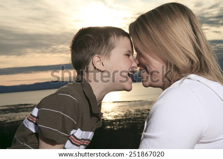 A portrait of a boy with is mother outside - stock photo