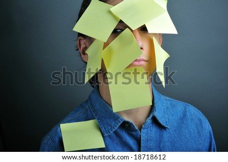 A portrait of a boy with yellow notes on face - stock photo
