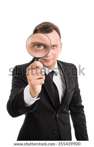 A portrait of a businessman looking through a magnifying glass, isolated on white background.