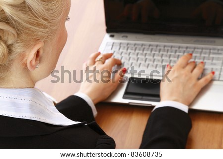 A portrait of a businesswoman sitting at a desk with a laptop,  back view