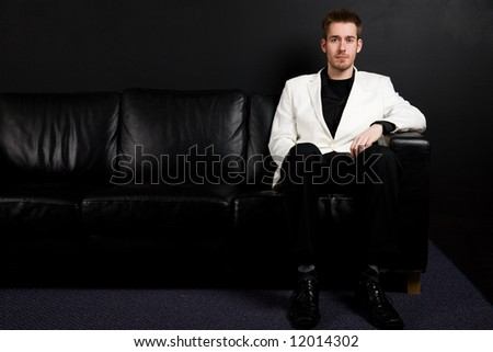 A portrait of a casual caucasian businessman sitting on a couch