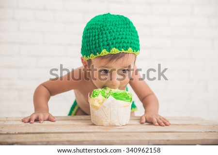 A portrait of a caucasian boy eating a cake, wearing green knit hat - stock photo