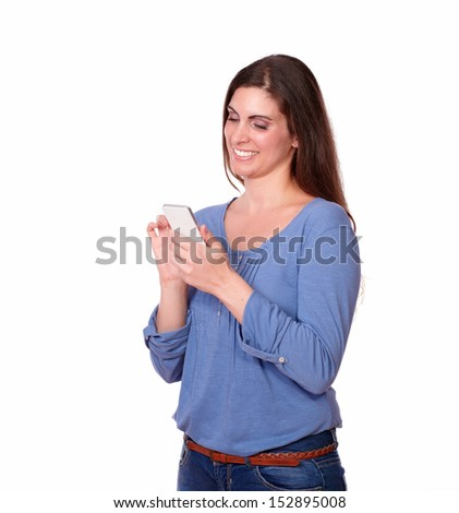 A portrait of a charismatic young lady on blue shirt standing and texting with her phone on isolated background