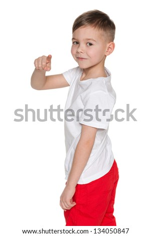A portrait of a cheerful boy pointing back