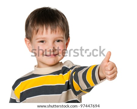 A portrait of a cheerful little boy holding his thumb up; isolated on the white background - stock photo