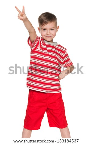 A portrait of a cheerful little boy in red shows victory sign; on the white background