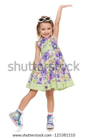 A portrait of a cheerful little girl makes a hand gesture; isolated on the white background - stock photo