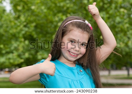 A portrait of a cheerful little girl outdoor with her thumbs up - stock photo