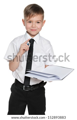 A portrait of a clever young boy in white shirt with a notebook and a pen on the white background