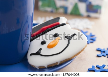 A portrait of a close-up snowman biscuit on the side of a blue mug - stock photo