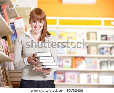 A portrait of a college student holding books in the library - stock photo