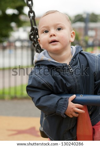 A portrait of a cute baby toddler or a small child, boy or girl, on a swing at the playground