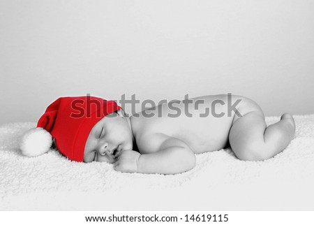 A portrait of  a cute baby wearing a santa hat, black and white with color restored in hat - stock photo