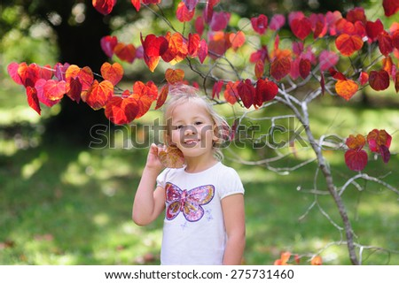 A portrait of a cute child, adorable little girl with blonde hair holding a heart shaped leaf standing in front of a pretty tree with red leaves in a garden - stock photo