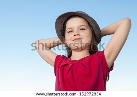 A portrait of a cute little girl, she is standing outside, wearing a hat and a red shirt against a blue sky, her arms are crossed behind her head, she looks relaxed and confident - stock photo