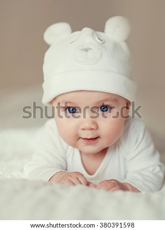 A portrait of a cute newborn baby in a white like a bear cub hat lying on its stomach and laughing