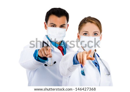 A portrait of a female and male doctors wearing masks and pointing with their fingers at you, flue season, restricted or hazardous area, isolated on a white background. health care teamwork. - stock photo