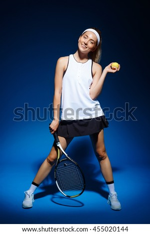 A portrait of a female tennis player with a racket and ball posing in studio - stock photo