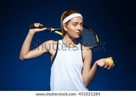 A portrait of a female tennis player with a racket on the shoulder holding ball in hand posing in studio - stock photo