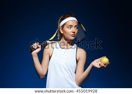 A portrait of a female tennis player with a racket on the shoulder holding ball posing in studio - stock photo