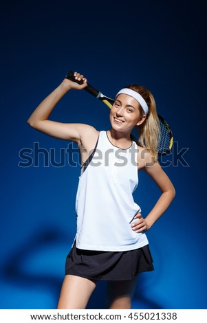 A portrait of a female tennis player with a racket on the shoulder posing in studio - stock photo