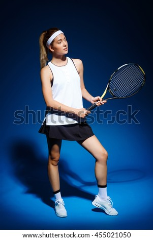 A portrait of a female tennis player with a racket posing in studio - stock photo