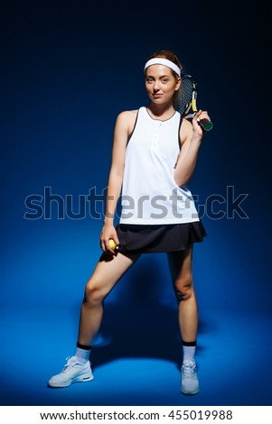 A portrait of a female tennis player with racket on the shoulder and ball in hand posing in studio - stock photo