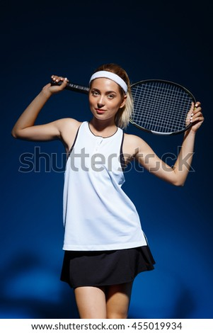 A portrait of a female tennis player with racket posing in studio - stock photo