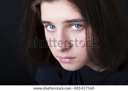 A portrait of a handsome blue eyes teenager on dark background