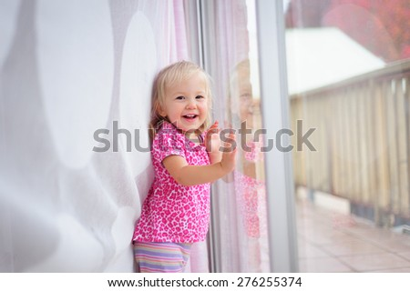 A portrait of a happy child, cute little baby or toddler girl hiding behind the curtain near the glass window - stock photo