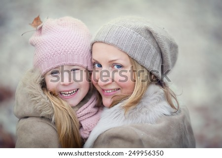 A portrait of a happy family: a young beautiful woman with her little cute daughter walking in the winter city park. - stock photo