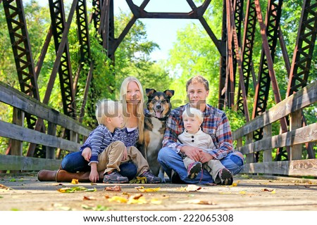 A portrait of a happy family of four people, including mother, father, young child, and baby brother and their pet German Shepherd Mix dog sitting outside on a bridge with the fallen leaves in Autumn. - stock photo