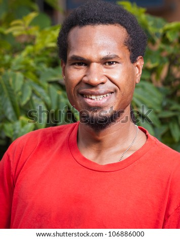 A portrait of a happy handsome young dark skinned man - stock photo