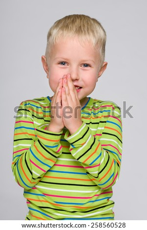 A portrait of a happy little boy in a striped shirt on the gray background - stock photo