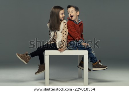 A portrait of a laughing girl and a smiling boy. Autumn style  - stock photo