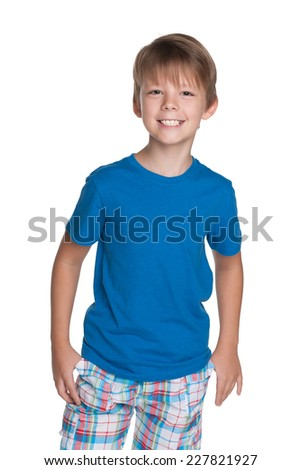 A portrait of a laughing young boy in a blue shirt on the white background