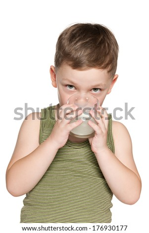 A portrait of a little boy with a glass of milk against the white background