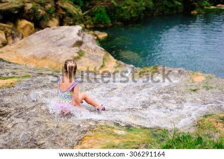 A portrait of a little girl wearing a colourful swimming suit sitting in the flowing water of Vanuatu cascades with her back turned to the camera - stock photo