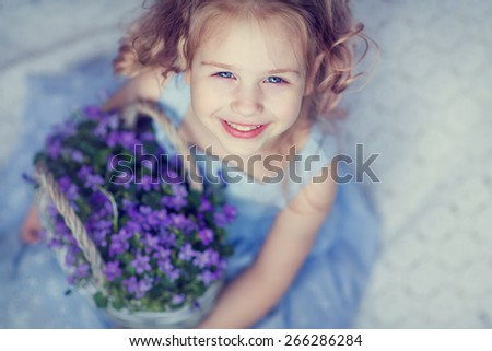 A portrait of a little sweet smiling girl holding a basket full of bluebells - stock photo