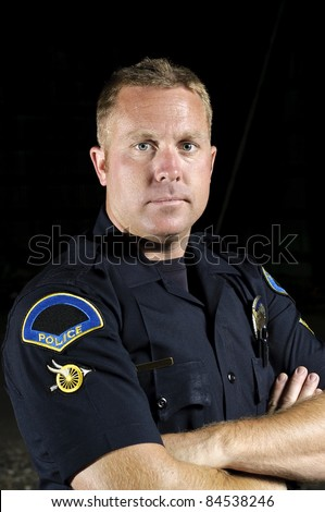 a portrait of a male police officer with his arms crossed.