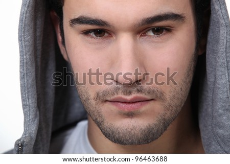 A portrait of a man with a hood on. - stock photo